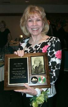 A smiling woman holding a plaque.